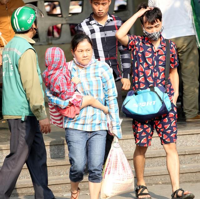 Trong khi đó, bà mẹ này xách một bao tải gạo nặng trĩu tay di chuyển ra khu vực chờ xe buýt.