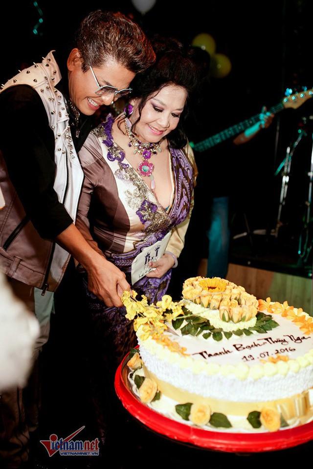 Hình ảnh cặp đôi cắt bánh cưới trong một tiệc cưới.