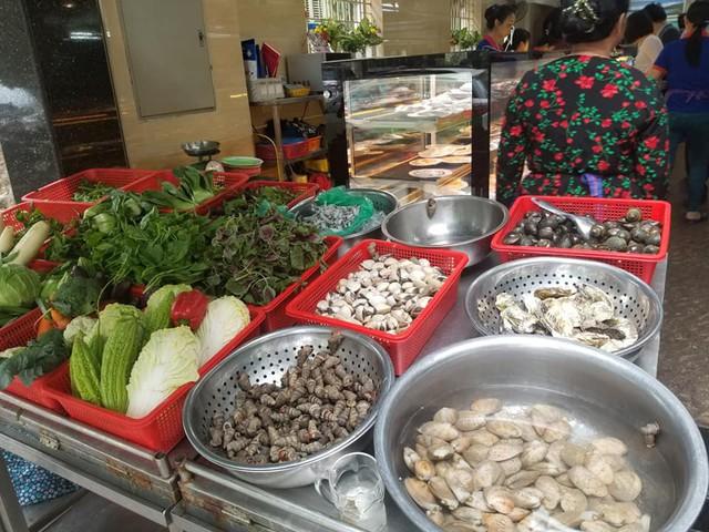 Hải sản tươi và rau được trưng bày tại kệ ngay cửa vào của quán.