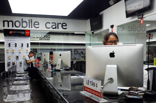 Bên trong cửa hàng có từ 3 - 4 nhân viên và một vài khách hàng đến nhận lại máy bảo hành.
