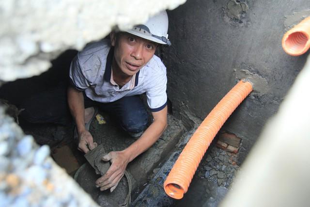 Anh Nguyễn Ngọc Lưu vừa nhanh tay xúc xi măng chát vào các lỗ nhỏ để cải tạo hệ thống thoát nước khu vực phố Cầu Mâu, vừa trò chuyện với PV.