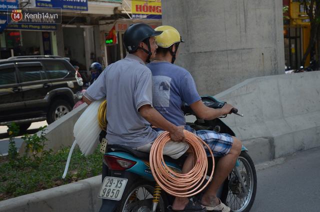 Nắng nóng đỉnh điểm ở Hà Nội, thợ điều hòa kiếm tiền triệu mỗi ngày - Ảnh 2.