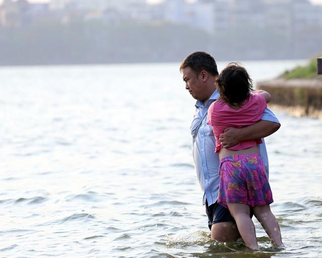 Một bé gái ôm chặt bố khi được cho xuống tắm tại Hồ Tây.