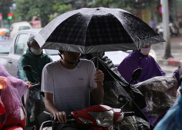 Một người đàn ông điều khiển xe máy phải dùng ô che mưa.