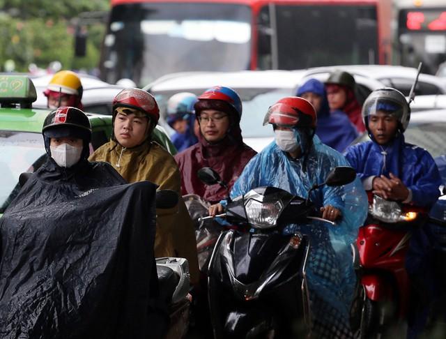 Người dân di chuyển bằng xe máy đứng chờ đèn đỏ dưới cơn mưa tại ngã tư Khuất Duy Tiến - Lê Văn Lương.