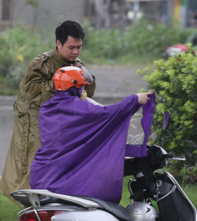 Đôi vợ chồng dừng xe máy dưới gầm cầu đi bộ mặc vội áo mưa.