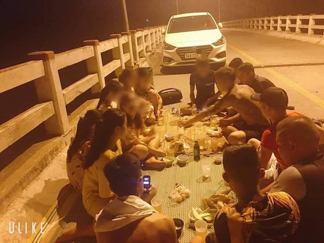 Nhóm thanh niên trải chiếu ngồi trên cầu ăn uống (Nguồn: KSĐP).
