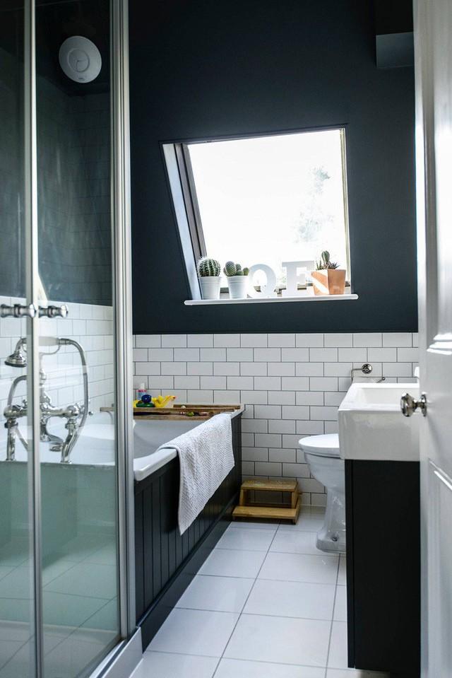Một phòng tắm gác mái nhỏ thanh lịch với gạch lát màu trắng, bồn tắm phủ đen và bồn rửa.