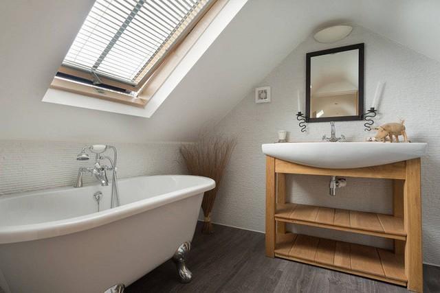 Phòng tắm gác mái hiện đại với bàn trang điểm bằng gỗ, bồn tắm có chân bằng bạc và một bồn rửa tay hiện đại.