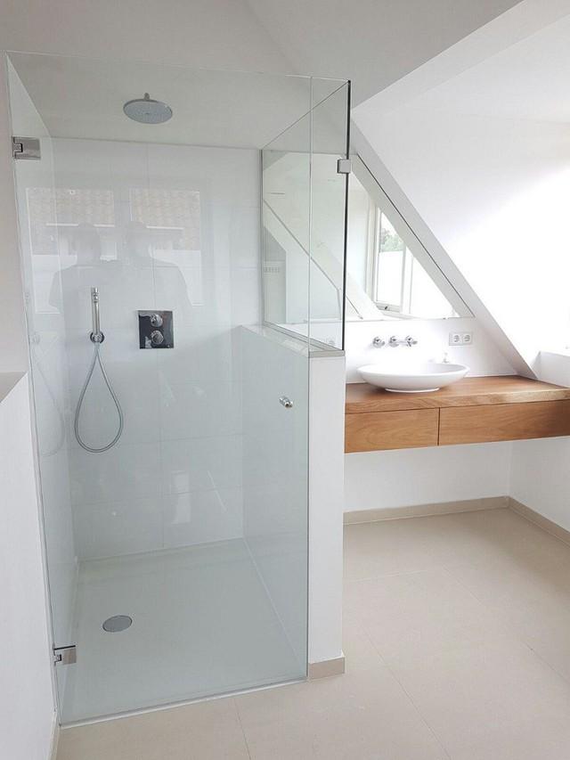 Phòng tắm gác mái tối giản với bàn trang điểm nổi bằng gỗ và vòi hoa sen trắng.