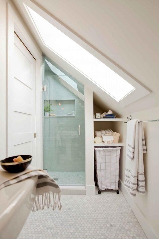 Một phòng tắm gác mái trung tính với không gian tắm được thiết kế từ gạch thủy tinh, gạch đá cẩm thạch trên sàn và giếng trời lớn.