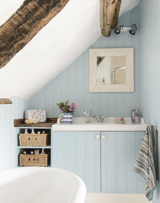 Một phòng tắm gác mái nhỏ màu xanh với dầm gỗ, giỏ để lưu trữ và một bồn tắm ngồi.