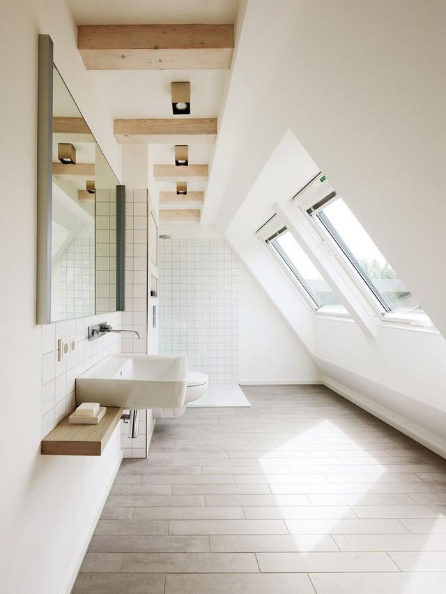 Một phòng tắm gác mái thoáng mát và tối giản với không gian tắm và bàn trang điểm nổi cộng với một số chi tiết bằng gỗ.