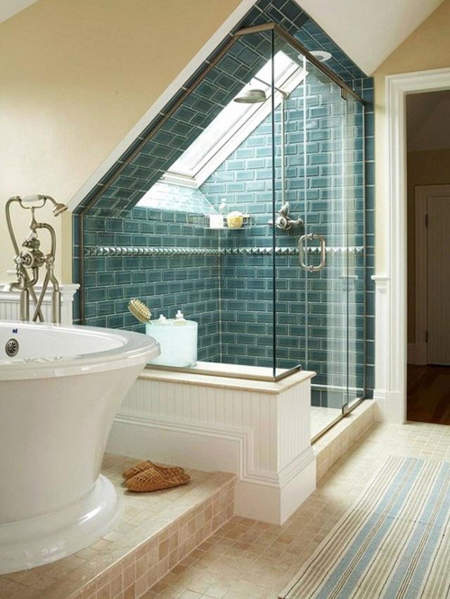 Một phòng tắm gác mái với không gian tắm bằng vòi sen với gạch màu xanh và một tấm thảm họa tiết sọc.