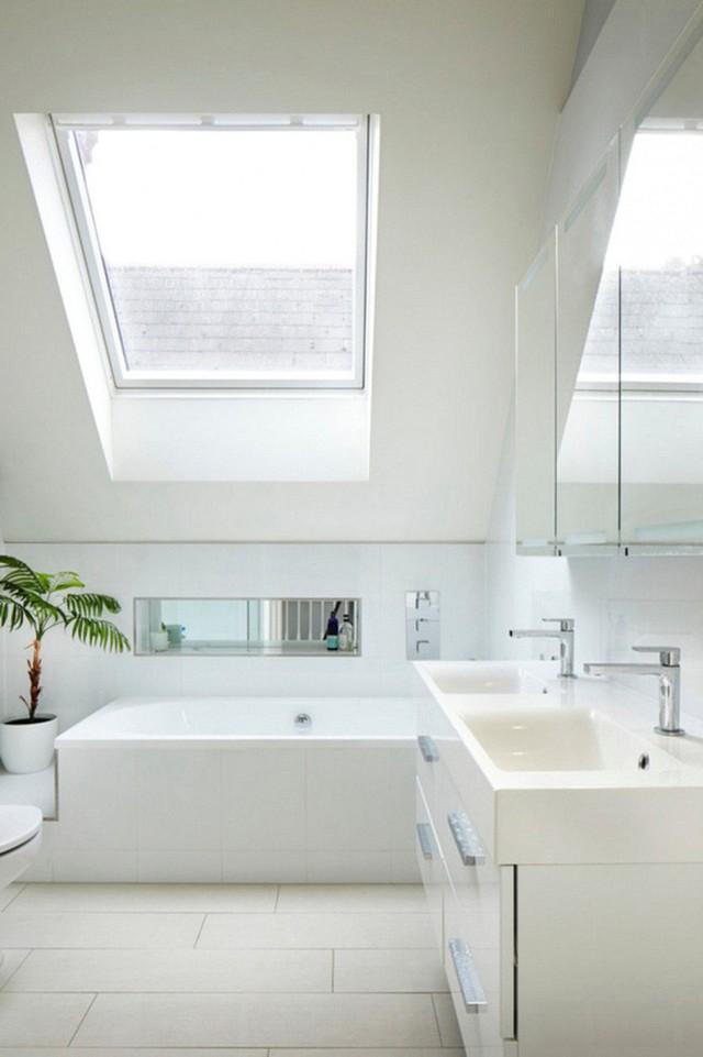 Không gian trắng sáng với sự điểm xanh tự nhiên từ chậu cây cảnh kết hợp cùng với giếng trời lớn cho phòng tắm gác mái này cảm giác thư giãn đến tuyệt vời.
