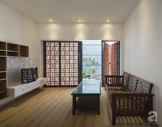 Phòng khách giản đơn với điểm nhấn từ khung cửa gập kết hợp gạch hoa gió.