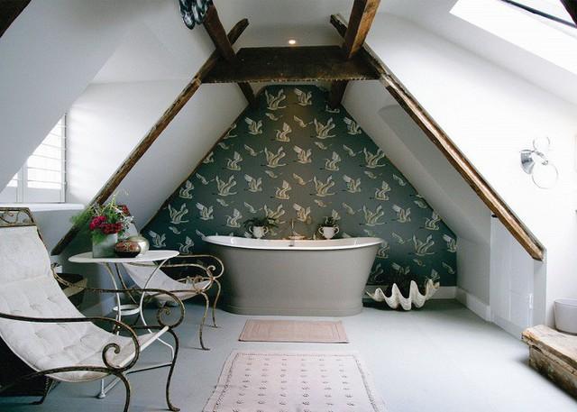 Một phòng tắm gác mái thanh lịch bao gồm: bức tường có hình nền họa tiết, một bồn tắm màu xám, những chiếc ghế trang nhã và chậu hoa cảnh.