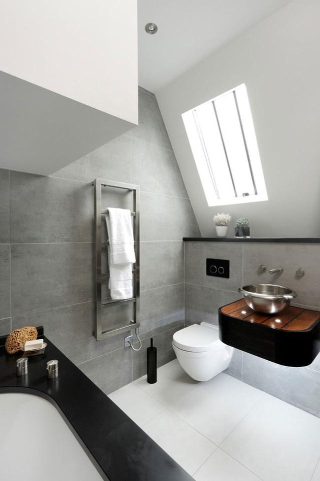 Phòng tắm gác mái táo bạo với gạch màu xám, bàn trang điểm nhỏ màu đen, bồn tắm viền đen và sàn nhà màu trắng.