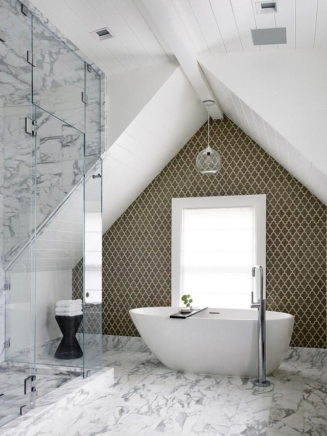 Một phòng tắm gác mái trang nhã với gạch đá cẩm thạch, bồn tắm hình bầu dục, bức tường gạch có họa tiết hấp dẫn.
