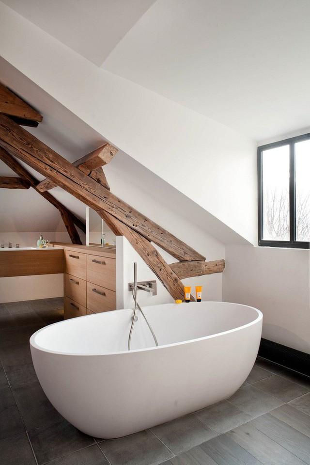 Phòng tắm hiện đại xen kẽ cảm giác mộc mạc với dầm gỗ, bồn tắm hình bầu dục và tủ màu trắng.