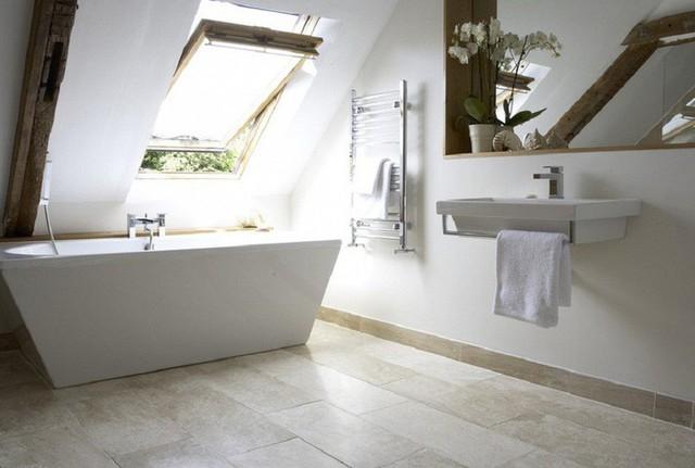 Phòng tắm gác mái tối giản với bồn tắm điêu khắc, bồn rửa tay nổi nhỏ, gương và một số đồ gỗ trang trí.