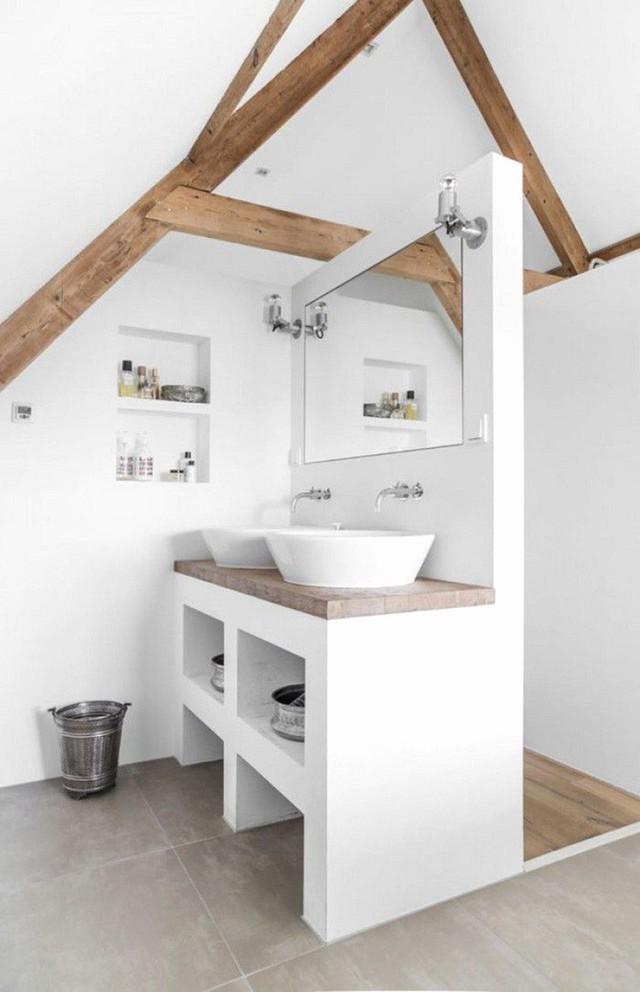 Phòng tắm gác mái màu trắng hiện đại với dầm gỗ và mặt bàn cộng với không gian lưu trữ tích hợp.