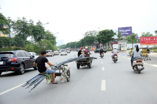 Sau nhiều phút lưu thông trên đường Võ Chí Công, chiếc xe ba gác tự chế bất ngờ cắt ngang tuyến phố, rẽ ngang vào phố mới, hướng khu Ngoại giao đoàn.