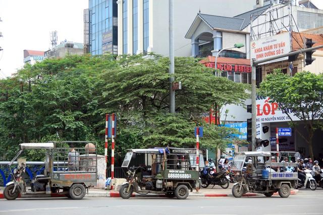 Xe ba gác xếp hàng tại khu vực lòng đường Lê Văn Lương, sẵn sàng cho những chuyến hàng mới trong ngày.