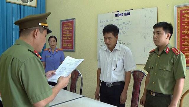 Ông Trần Xuân Yến, phó giám đốc Sở GD-ĐT tỉnh Sơn La (áo trắng), nghe tống đạt quyết định khởi tố bị can. Ảnh: NH
