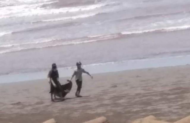 Người dân ven biển đưa thi thể vào bờ.