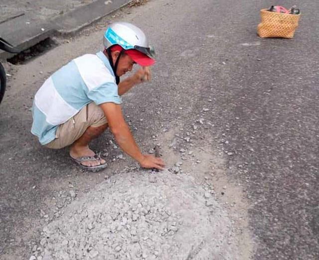 Sợ người đi đường sẽ gặp nạn với khối bê tông rơi vãi giữa đường, anh thợ đá đã nán lại hì hục đục phá