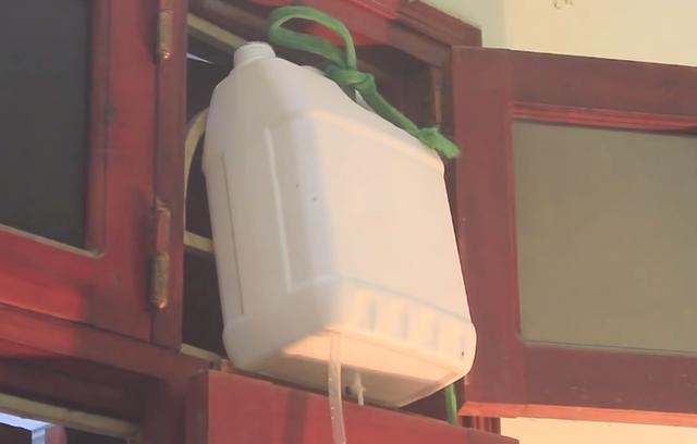 Kết nối ống nhựa vào can nhựa và đặt can có nước từ trên cao tạo áp lực chảy xuống.