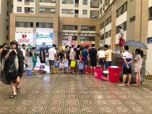 Người dân tại chung cư Tân Tây Đô đội mưa xếp hàng để lấy nước. Ảnh: Bảo Loan