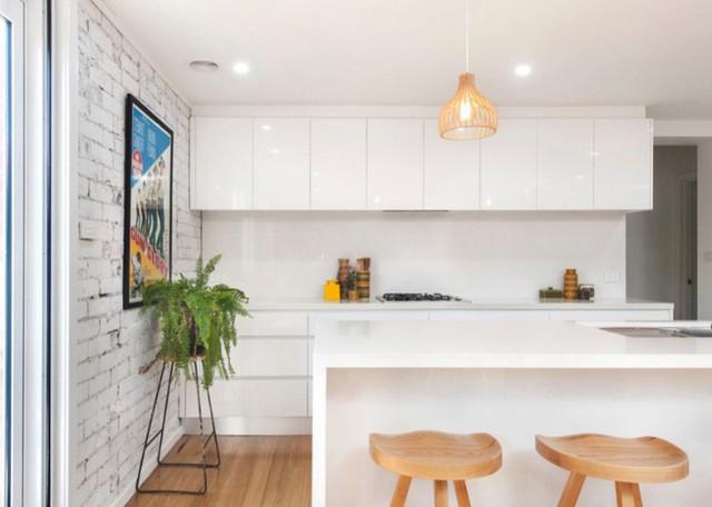 Một nhà bếp theo phong cách tối giản mở ra phần còn lại của khu vực sinh hoạt.