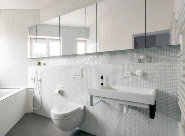 Một bức tường dài bằng gương có chức năng lưu trữ và phản chiếu ánh sáng từ các cửa sổ.
