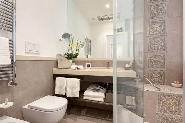 Đá và gạch cao cấp kết hợp với chất liệu gỗ kỳ tạo ra một trải nghiệm phòng tắm nhỏ sang trọng ở Rome.