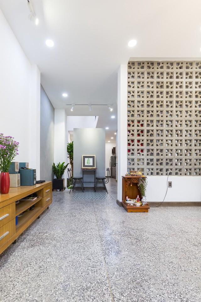 Những bức tường bằng gạch bông gió ngăn cách phòng khách nơi tầng trệt với khu vực thông tầng cũng góp phần làm nên màn hoa nắng cho phòng khách. Sàn nhà lát đá mài giúp không gian luôn mát mẻ, kể cả giữa trưa khi thời tiết nắng nóng.