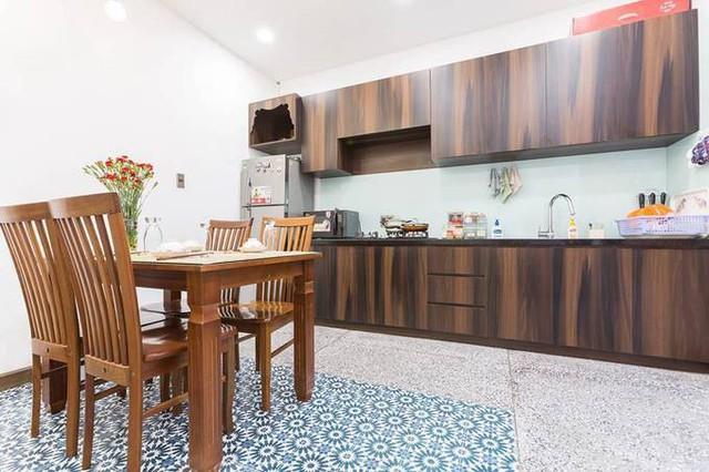 Bếp và phòng ăn nằm cuối tầng trệt, ngay bên cạnh giếng trời. Tấm thảm bằng gạch hoa dưới bàn ăn, giống tấm thảm ở khu vực sinh hoạt chung bên cạnh chân cầu thang, giúp tầng trệt ngôi nhà có đươc sự đồng nhất trong trang trí.