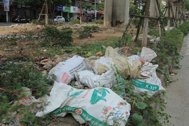 Rác thải xây dựng được đựng trong các bảo tải và nằm ngổn ngang trên vỉa hè phố Yên Lãng, đoạn gần khu vực trường Tiểu học Thái Thịnh.
