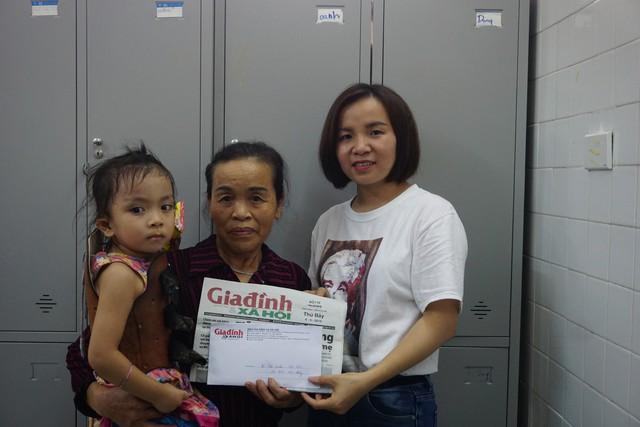Phóng viên Phương Thuận - đại diện Chương trình Vòng tay nhân ái (Báo Gia đình và Xã hội) trao số tiền 14.915.000 đồng của bạn đọc hảo tâm cho gia đình bé Tuệ Linh