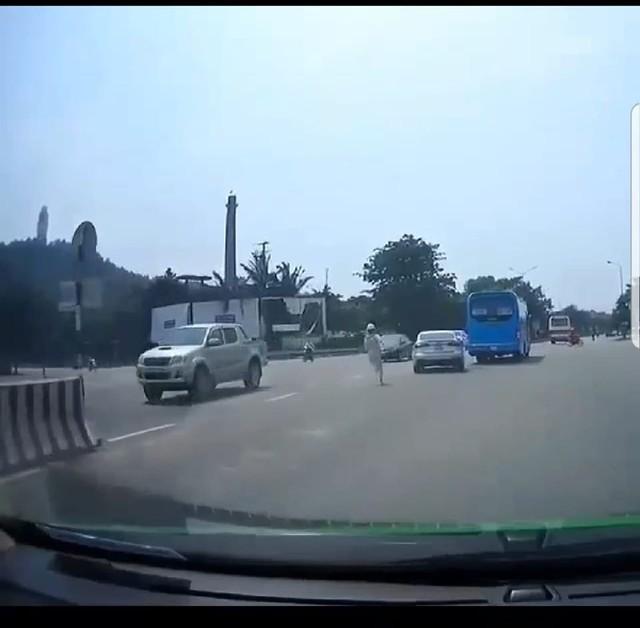 Mặc dù nhiều xe qua lại nhưng nam nhân viên vẫn cố đuổi theo chiếc xe con trốn vé. Ảnh cắt từ clip.