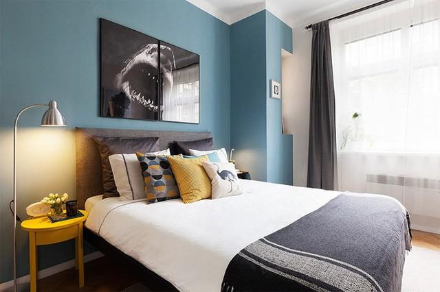 Phòng ngủ chính được sơn màu xám nổi bật với các điểm nhấn màu vàng và bức tường đầu giường được sơn màu xanh nước biển.