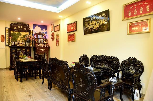 Phòng khách và bàn thờ gia tiên bằng gỗ quý, cộng với bộ bàn ghế được chạm trổ tinh vi