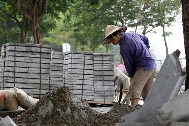 Những công nhân tại công trường cải tạo, chỉnh trang hè phố bằng đá tự nhiên, ở phố Trích Sài (quận Tây Hồ, Hà Nội).