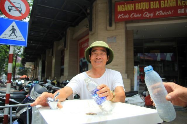 Mấy hôm nay trời nắng nóng, ông Nguyễn Văn Tân, quê ở Hà Nam, mưu sinh bằng nghề xe ôm ở khu vực quận Hoàn Kiếm cũng tranh thủ chạy đến cây nước sạch ở cổng chợ hàng Da lấy nước để tiết kiệm chi tiêu.