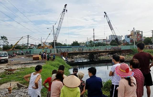 Nhiều người theo dõi cơ quan chức năng đưa thi thể người phụ nữ lên bờ. Ảnh: Nguyễn Huy.