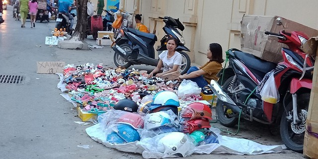 """Cứ mỗi buổi chiều trên đường Tam Trinh (Hoàng Mai, Hà Nội) lại diễn ra cảnh họp chợ cóc. Ở đây, các mặt hàng như mũ bảo hiểm """"giá rẻ"""", giầy dép, đồ lót lại được người dân bày bán la liệt ngay dưới lòng đường."""