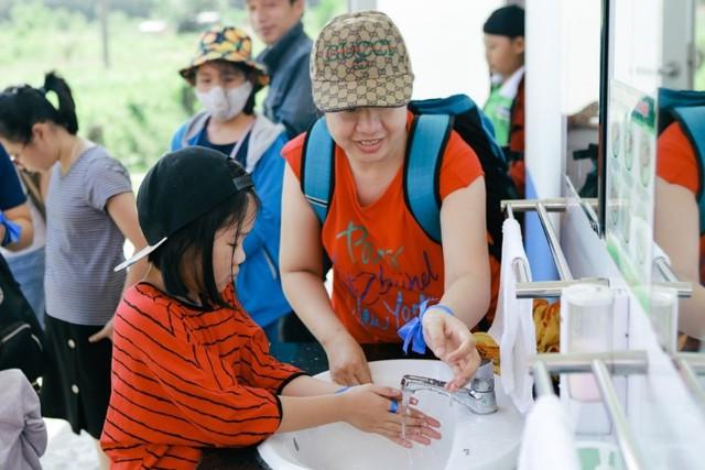 Các bạn nhỏ được bố mẹ hướng dẫn rửa tay cẩn thận trước khi vào tham quan Trang trại