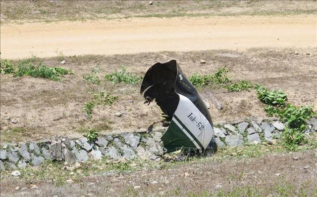 """Một mảnh vỡ của máy bay có mang ký hiệu """"Ika – 52"""", đây cũng là tên của một loại máy bay huấn luyện quân sự. Ảnh: Phan Sáu, Tiên Minh - TTXVN"""