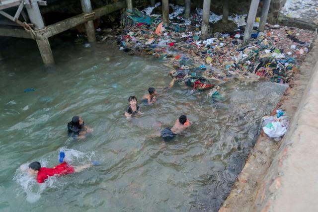 Trẻ em tắm chung với rác thải nhựa
